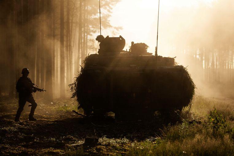 Een gecamoufleerde tank met Nederlandse militairen tijdens de oefening in 2018 in de bossen bij Pabrade in Litouwen.  Beeld Jasper Verolme