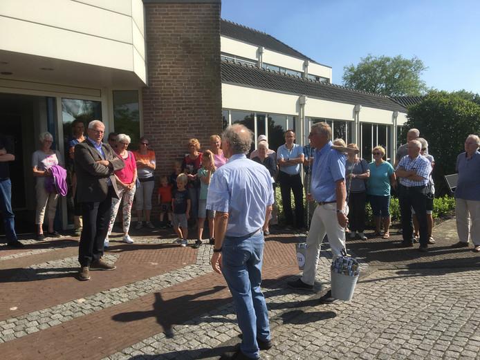 Goof Vogelaar van initiatiefgroep Binnenstebuiten sjouwt de emmers. Links wethouder Jan de Groot.