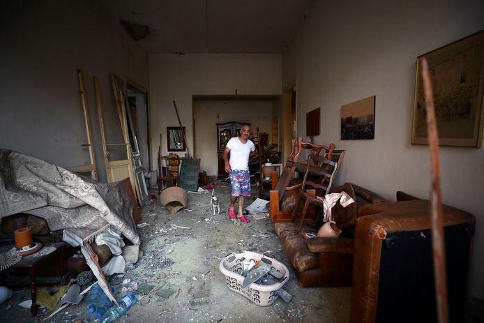 Een inwoner van Beiroet bekijkt zijn vernietigde huis.