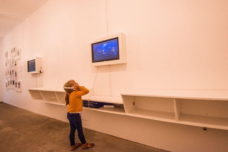 Een jonge bezoekster bekijkt een video in de Douviehoeve tijdens Kunstenfestival Watou .