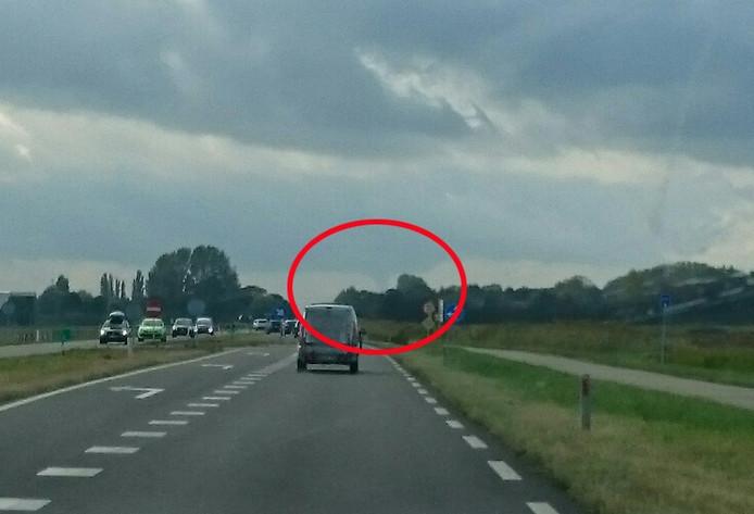 De N59 bij Oosterland. Rechts boven de auto bij de boom, is de windhoos te zien.