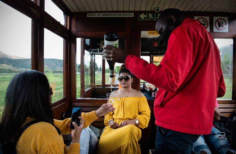Robson Soraidema schenkt de passagiers van de wijntram  wijn in.  Beeld Bram Lammers
