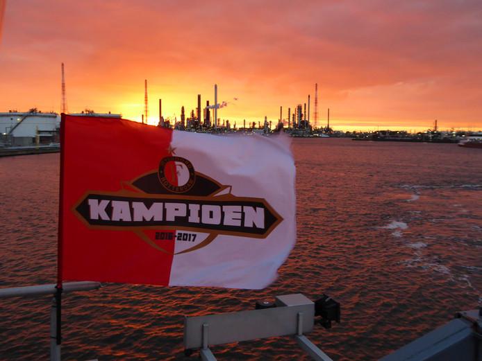 Kijk, vakantie is mooi, maar uiteindelijk moet er ook gewerkt worden. Marcel de Jong maakte deze schitterende foto van de Feyenoordvlag aan boord van motortankschip Odessa. Op de achtergrond de haven van Antwerpen.