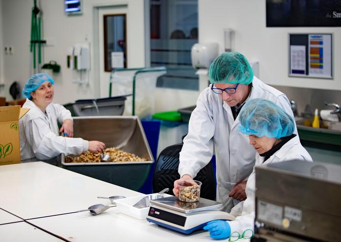 Juul Ellerman (groen haarnetje) tussen collega's op de foodafdeling van werkbedrijf Senzer in Helmond.