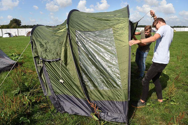 Max Klabbers (links) en  Lout Kuiper zetten hun tent op tijdens de introductieweek in Wageningen. Beeld Marcel van den Bergh