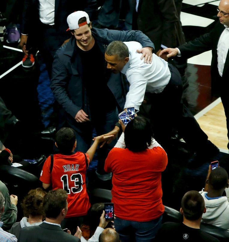 President Obama begroet fans in de pauze van de NBA-wedstrijd. De burgemeester van de stad, Rahm Emanuel. Ligt flink onder vuur vanwege de behandeling van zwarte inwoners door agenten. Beeld Reuters