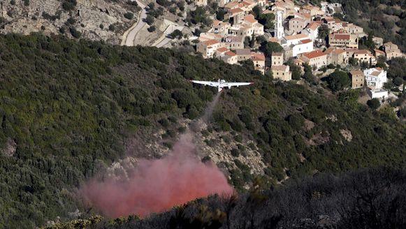 Een blusvliegtuig vliegt over de bossen bij Palasca op het eilandje Corsica.