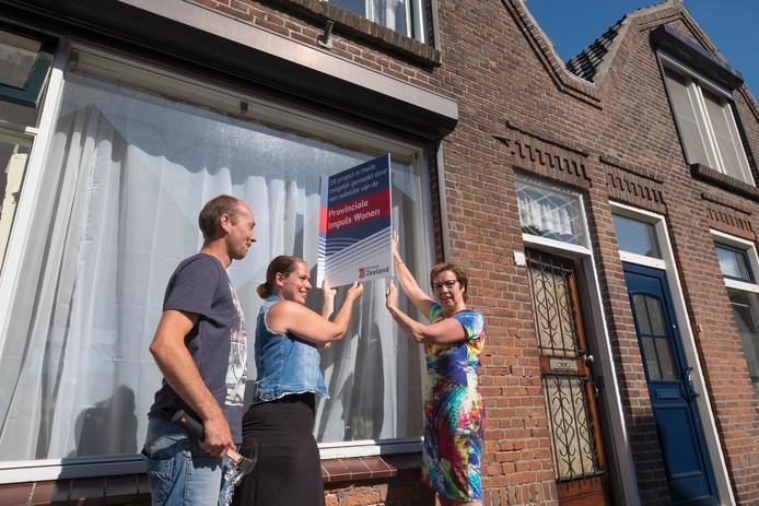 Silvio en Marien Kramer ontvangen het bord van Carla Schönknecht in Oost-Souburg. Met die subsidie kunnen ze twee huizen samenvoegen.