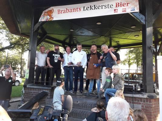 Zjef Naaijkens maakt vanaf de kiosk van HIlvarenbeek bekend welk bier Brabants lekkerste is. Hij wordt geflankeerd door de genomineerde brouwers en, helemaal links, Brabants Dagblad-hoofdredacteur Lucas van Houtert.