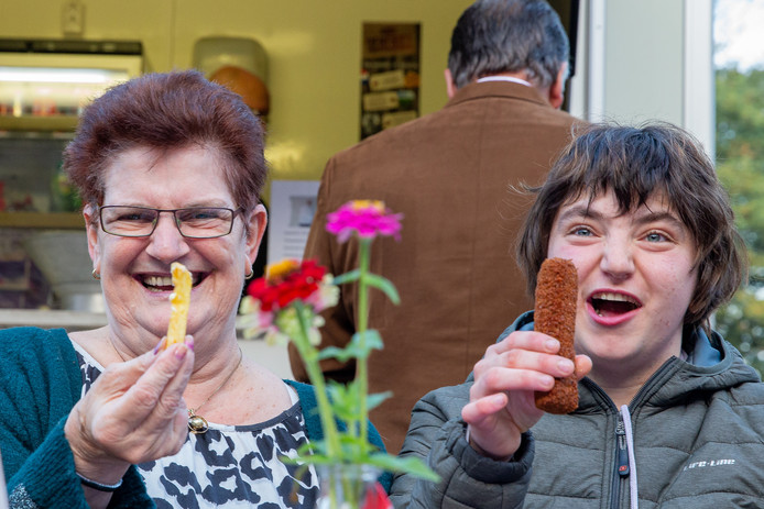 Bewoners Thea (links) en Loes van zorgboerderij De Hagert genieten van een kroket en een frietje.