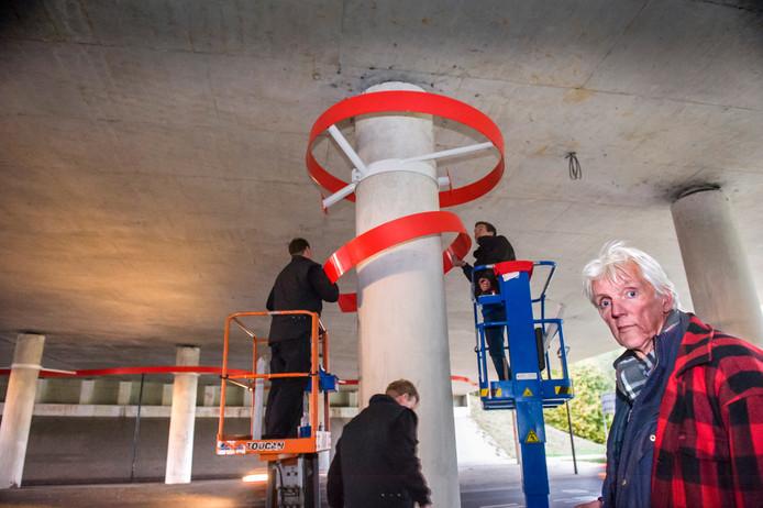 Wouter Brave ziet toe op de installatie van zijn kunstwerk onder het tunneltje.