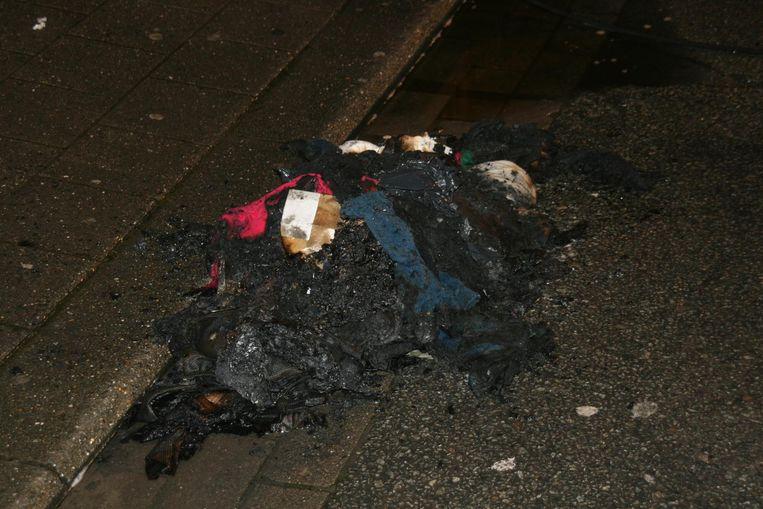 Het hoopje kleren dat in de kelder van het flatgebouw in brand werd gestoken.