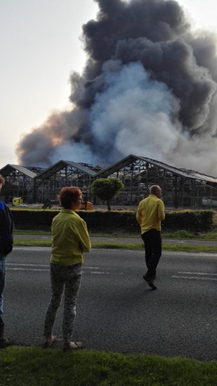 De eigenaar van Fonteyn Outdoor (r) kijkt machteloos toe bij de brand in Uddel