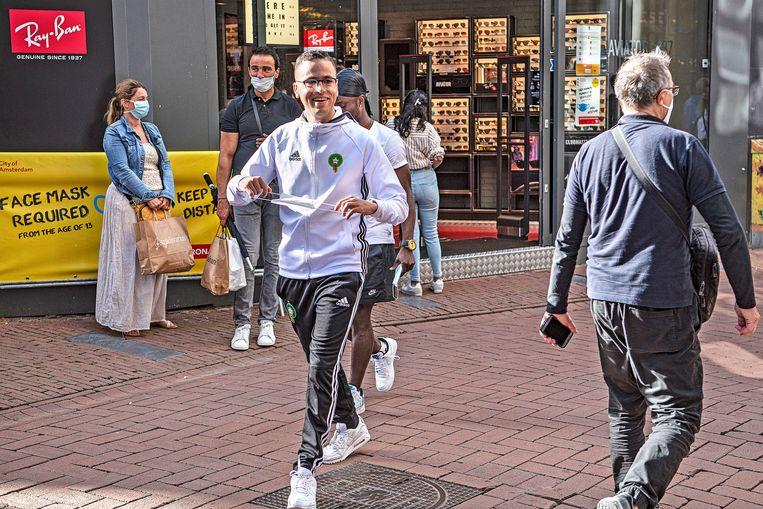Veruit de meeste mensen zetten braaf hun mondkapje op bij het betreden van de straat, maar een paar honderd meter verderop hangt het in veel gevallen alweer op de kin Beeld Guus Dubbelman / de Volkskrant