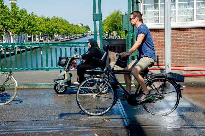 Een brug in Amsterdam wordt besproeid om hem een beetje koel te houden.