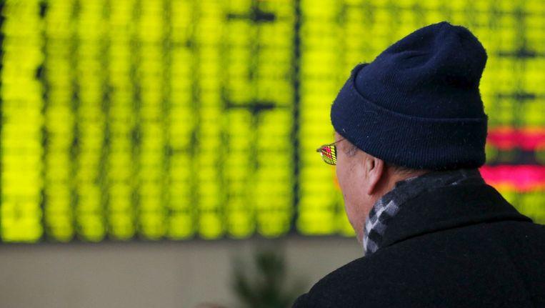 Een Chinese handelaar bekijkt de beurs in Nantong. Beeld reuters