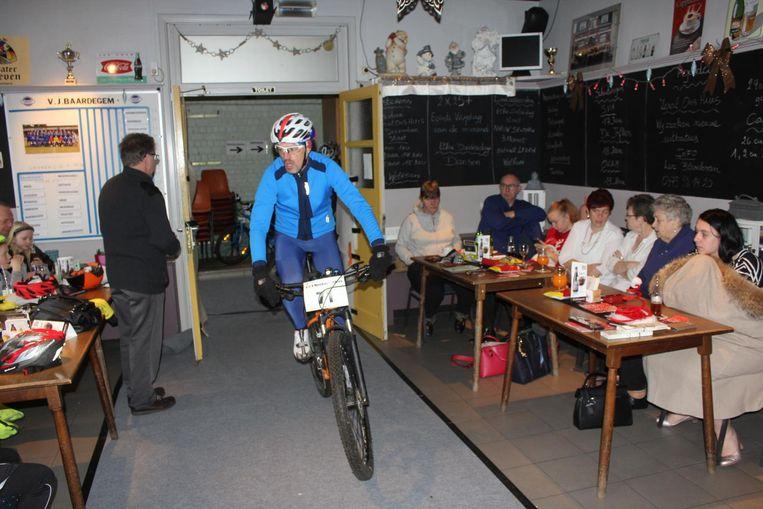 De renners fietsen door café Ons Huis in Baardegem.