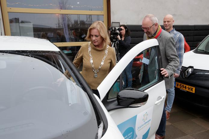 Burgemeester Vermeulen stapt in een elektrische wagen voor een proefritje.