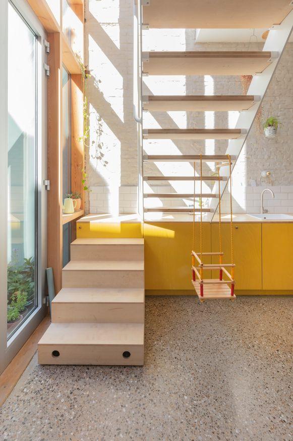 Opvallend is de keuken met gele fronten en de trap die gedeeltelijk over het aanrecht loopt.