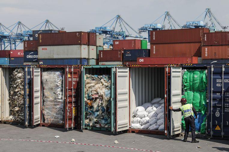 Een Maleisische agent onderzoekt containers vol met plasticafval dat op het punt staat teruggestuurd te worden naar Australië. Beeld null