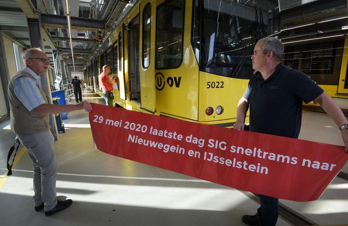 Gerard van Buuren en Remy den Hartog beplakken de tram met folie, voorzien van opdruk.