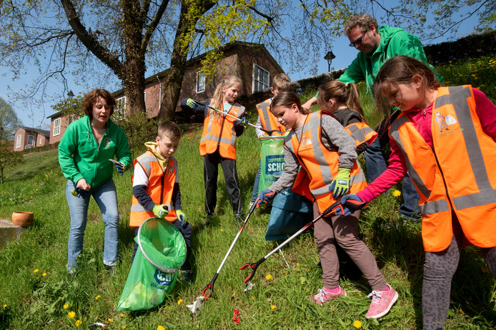 Oprichter Mike Hoose (tweede van rechts) van het Kinderwijkteam is deze week met een nieuwe lichting kinderen aan de slag gegaan om de leefomgeving in Klarendal schoner te maken.