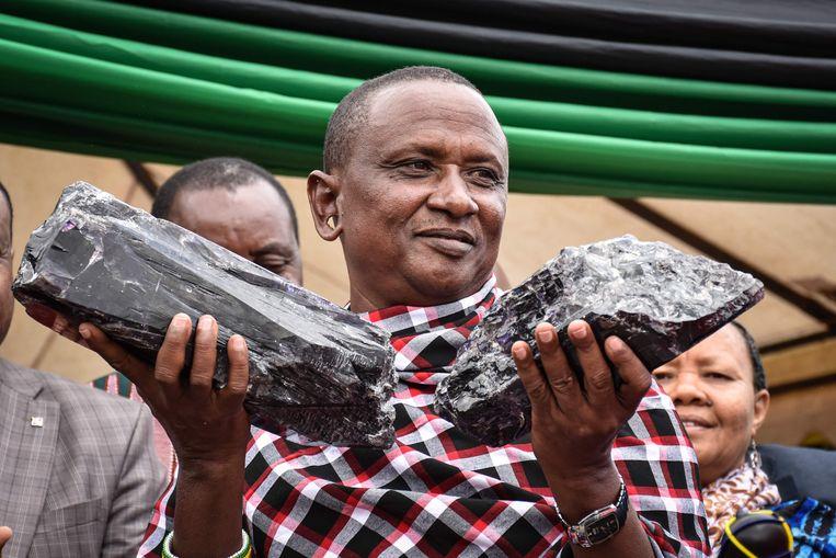 De Tanzaniaanse mijnwerker Saniniu Laizer houdt de twee grootste tanzaniet edelstenen omhoog die ooit zijn gevonden.  Beeld AFP