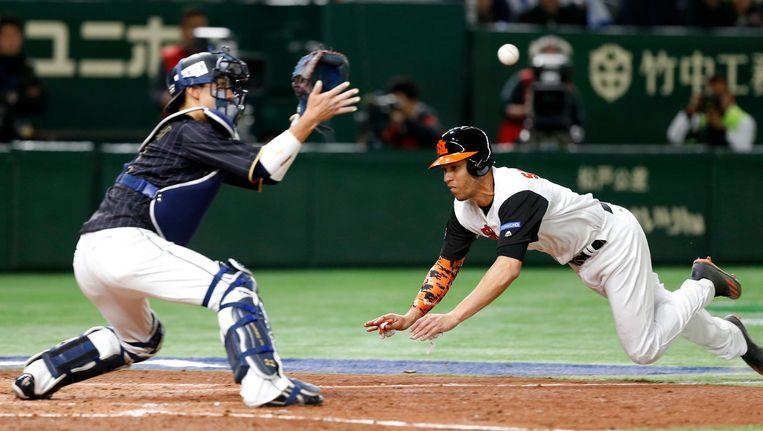 Andrelton Simmons duikt naar de thuisplaat in de wedstrijd tegen Japan op de World Baseball Classic in Tokio Beeld ap