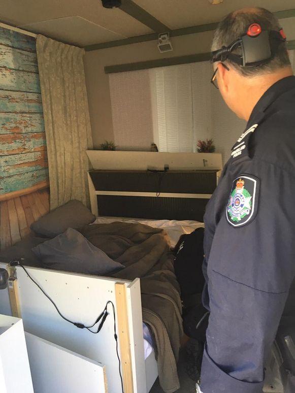 Een van de politieagenten tijdens het doorzoeken van de slaapkamer van de Huizenaar. Boven het hoofdeinde hangt de witte infraroodlamp die de insecten zogezegd moest buiten houden.