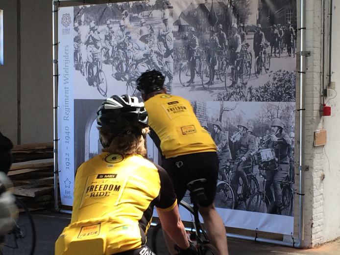 Op de achtergrond de grote billboards met daarop leden van het Regiment Wielrijders.