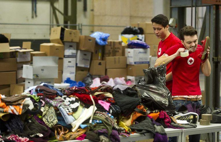 Vrijwilligers van het Rode Kruis sorteren spullen, zoals kleding en schoenen, ten behoeve van vluchtelingen. Beeld anp