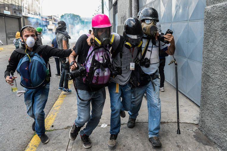 Een verwonde journalist wordt te midden van protesten in Venezuela in veiligheid gebracht. Beeld AFP