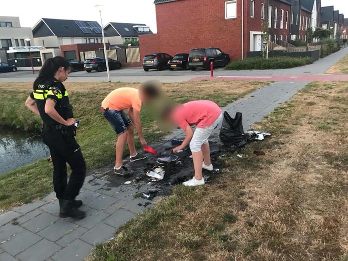 De twee jongens ruimen hun zooi onder het toezicht van een agente op.