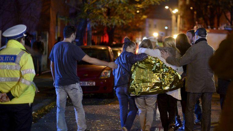 Mensen lopen vlak na de ramp voor de club in Boekarest. Beeld reuters