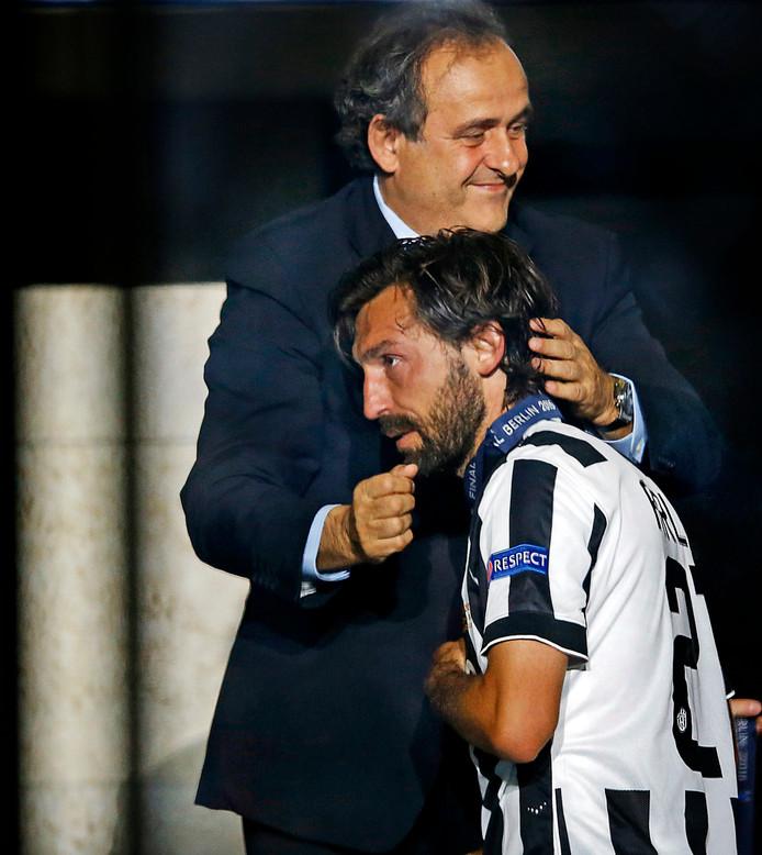 Michel Platini troost Andrea Pirlo na zijn verloren Champions League-finale tegen FC Barcelona in 2015.
