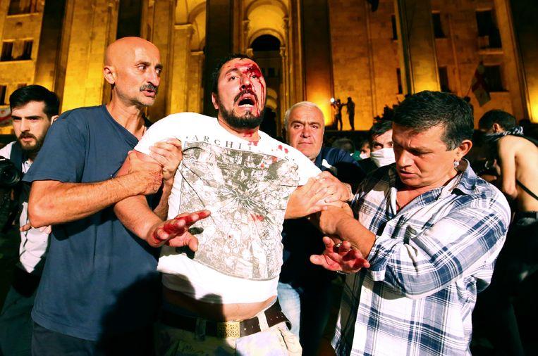 Een gewonde demonstrant wordt afgevoerd door een van zijn medestanders. Beeld AP