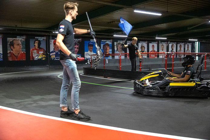 Hezemans-werknemers Wouter Kamperman (l) en Thomas Neve (midden) zwaaien met de vlaggen voor karter Quinten Ghazi, die voor het eerst in 3,5 maand weer kon karten in Eindhoven.