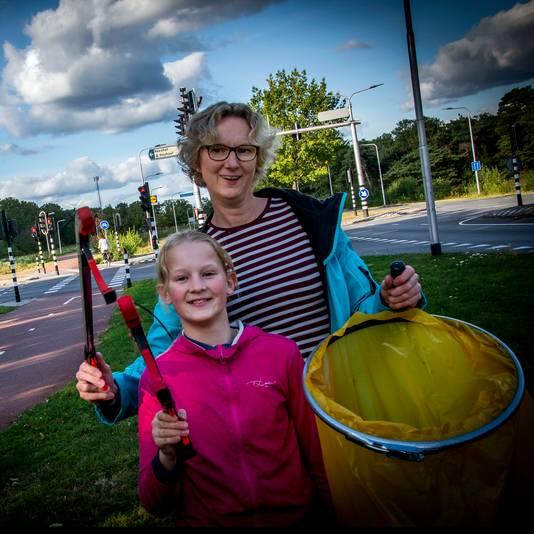 """Paula Mommersteeg en dochter Roos ruimen afval in de Reeshof. ,, En als je met de buurt of een paar straatbewoners aan de slag wil, komen ze een aanhanger brengen en ophalen."""""""