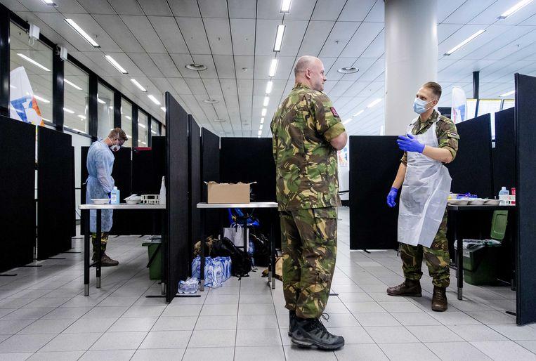 Militairen staan klaar om reizigers uit risicogebieden te testen op corona in de teststraat op Schiphol. Beeld ANP