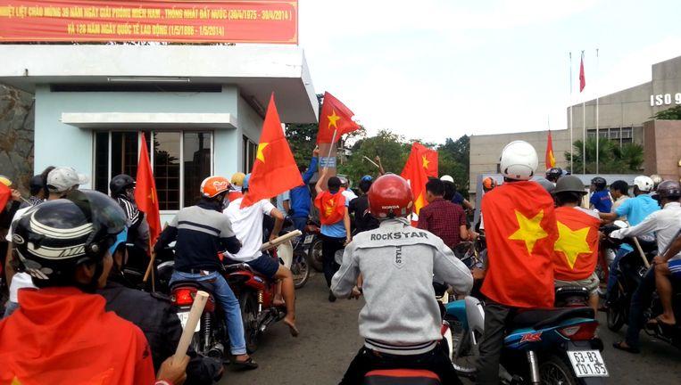 Betogers met Vietnamese vlaggen bij een fabriek in het zuiden van het land tijdens een ant-China-protest.
