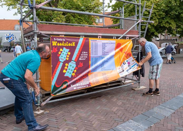 Mede-organisatoren Renny Minnaert (links) en Johan Wattel hangen het doek met de programmering op.