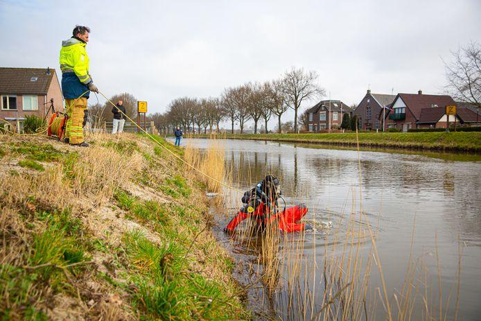 Een duiker van de brandweer Heerde gaat het water in.