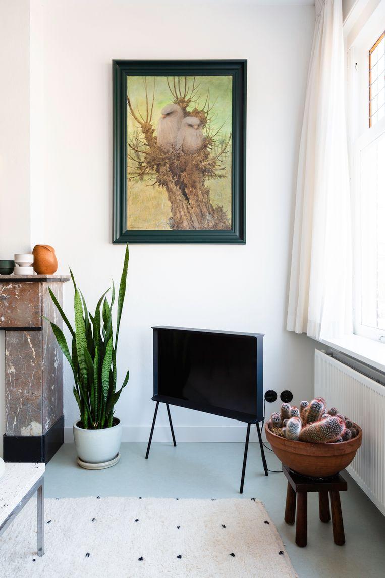 'Dit schilderij is van Henri Verstijnen, een vrij bekende schilder. Ik ken dat schilderij al mijn hele leven: het hing altijd bij mijn opa en oma. Het lijkt alsof er uilen op staan, maar het zijn kobolden, een soort fantasieachtige wezens. Ik zou het zelf niet in een galerie gekocht hebben, maar door de herinnering voelt het voor mij bijzonder. Op de grond ligt een superzachte moderne Berber, die we in Marrakech hebben gekocht.' Beeld Henny van Belkom