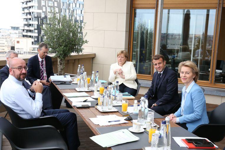 Een ander onderonsje: voorzitter van de Europese Raad Charles Michel (links) met tegenover zich aan tafel de Duitse bondskanselier Angela Merkel, de Franse president Emmanuel Macron en voorzitter van de Europese Commissie Ursula von der Leyen. Beeld EPA