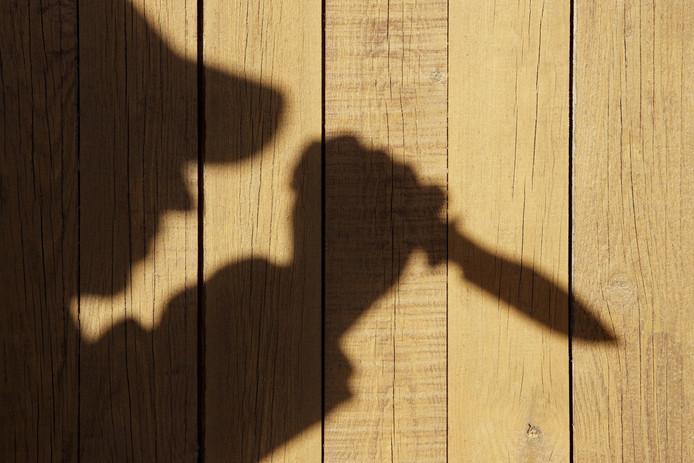 Een schaduw van een man met een mes. Dit is niet de man uit Winterswijk.