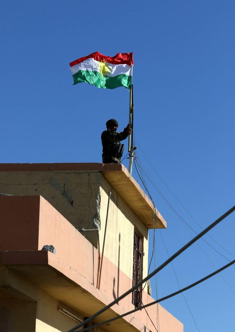 Een Koerdische strijder hijst zijn nationale vlag omhoog in de stad Sinjar. Beeld anp