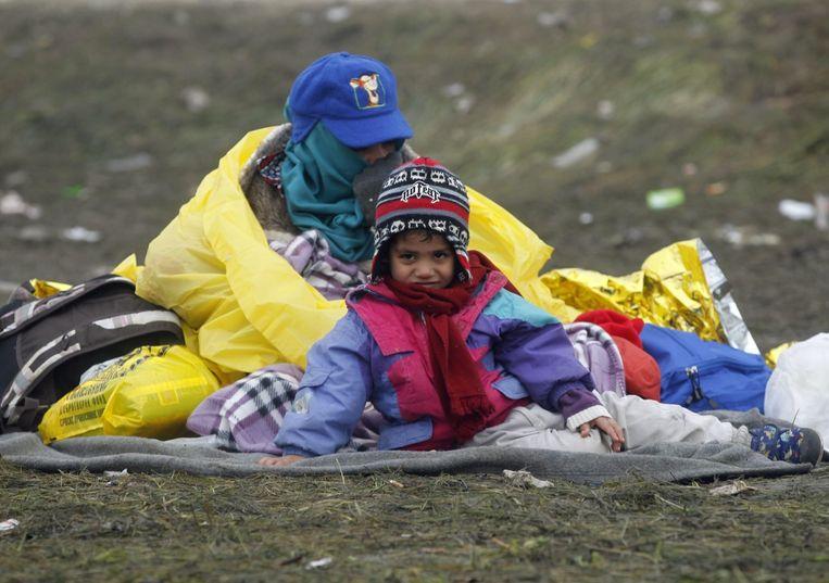 Wachtende vluchtelingen op een kleedje bij de grens tussen Slovenië en Kroatië. Beeld ANP