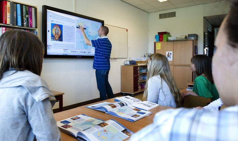 Een leraar geeft uitleg aan de klas op een digitaal schoolbord. Beeld anp