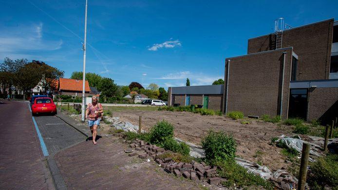 Het braakliggende terrein op de hoek Akkerstraat - Het Plein in Vlijmen, waar nu is gestart met bouwwerkzaamheden. Door de hekken rond het bouwterrein is het trottoir tijdelijk niet te gebruiken.