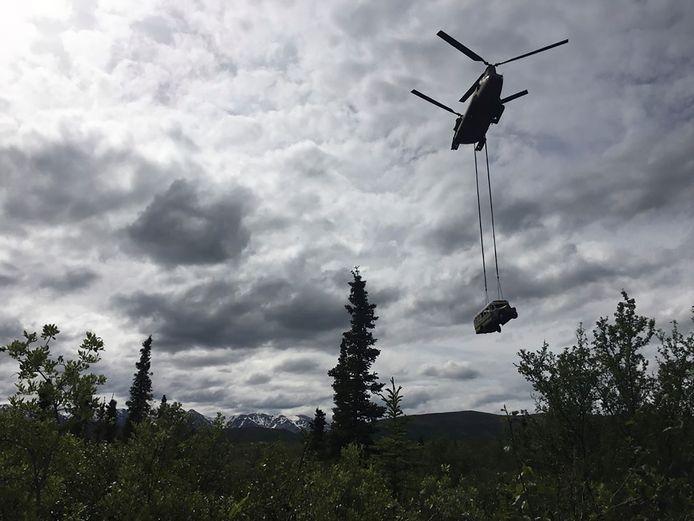 De bus wordt weggehaald door een helikopter.